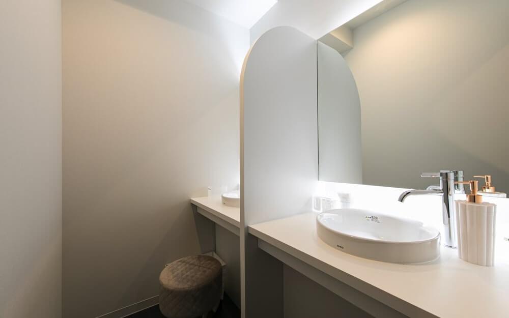 白を基調とし、鏡と洗面台と椅子があるグロウクリニック恵比寿院のパウダースペース