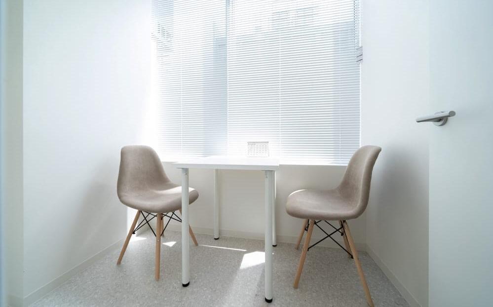 白を基調とし、椅子と机があるグロウクリニック池袋院のカウンセリングルーム