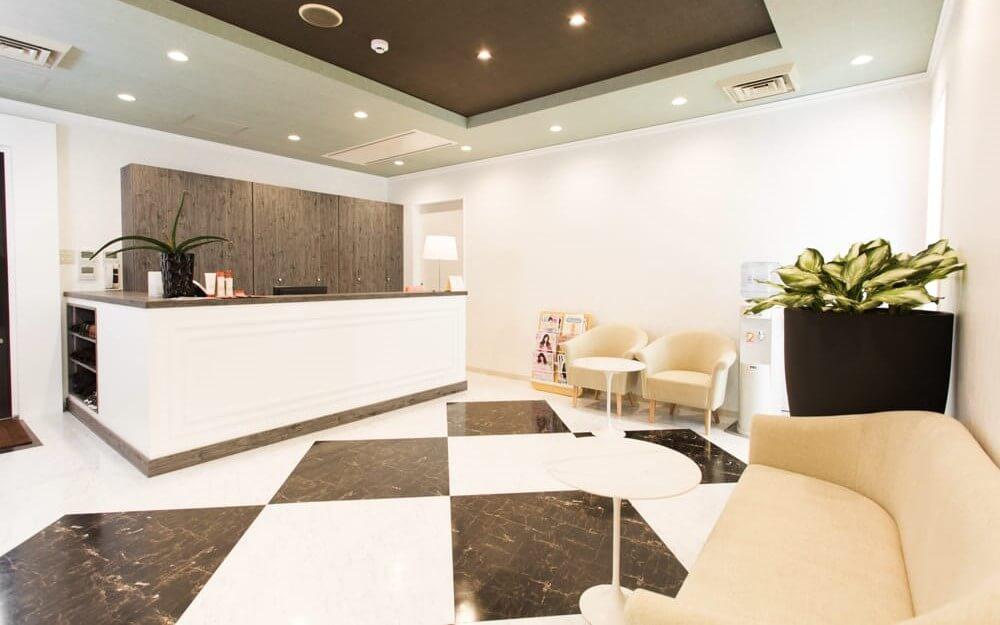 白と茶色を基調としたシックな雰囲気のグロウクリニック柏院の受付と待合室