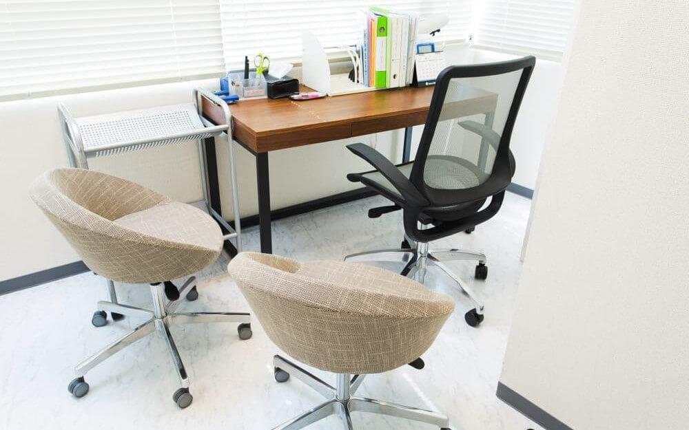 白を基調とし、椅子と机があるグロウクリニック柏院のカウンセリングルーム