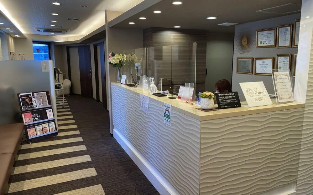 茶色と白を基調とした清潔感のあるグロウクリニック西新宿院の受付と待合室