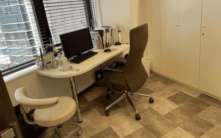 茶色と白を基調とし、椅子と机があるグロウクリニック西新宿院のカウンセリングルーム