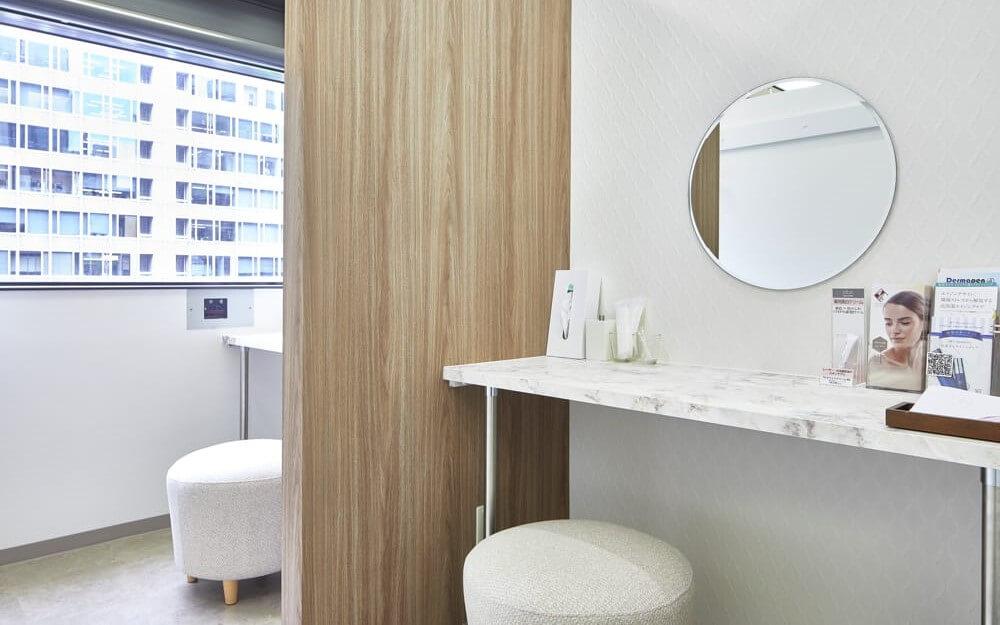 鏡と椅子と机があるグロウクリニック大阪北新地院のパウダースペース