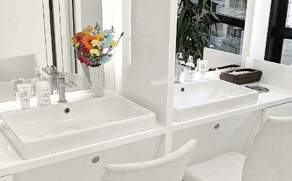白を基調とし、鏡と洗面台とライトと椅子があるグロウクリニック渋谷院のパウダールーム