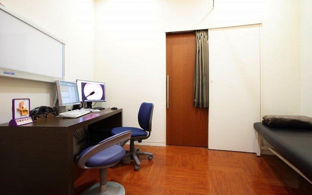 白と茶色を基調とし、椅子と机とベットがあるグロウクリニック渋谷新南口院の診察室