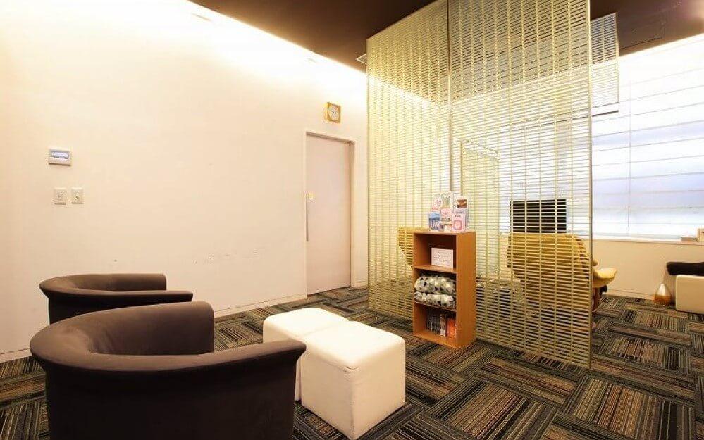 ソファ、毛布、読み物があるグロウクリニック渋谷新南口院の中待合室