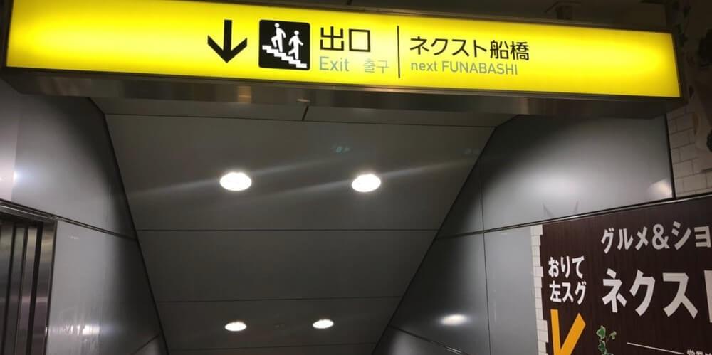 京成船橋駅の東改札口のすぐ横にあるネクスト船橋出口の階段の看板
